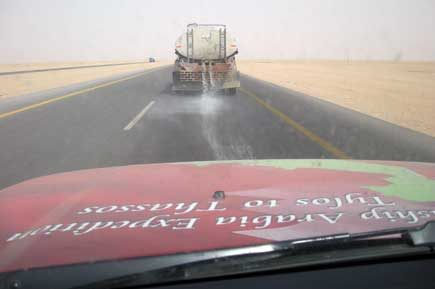 With outside temperatures well over 40C, a water truck cools the road to prevent the asphalt from melting