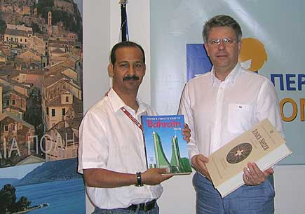 Ali, left, exchanges books with Sotirios Vosdou, Secretary General for the Region of Ionian Islands.