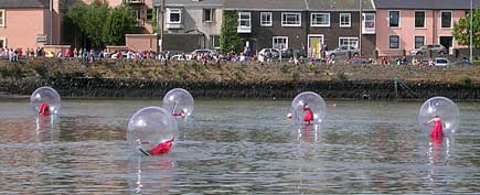 Dancers inside giant bubbles on the water enthrall spectators